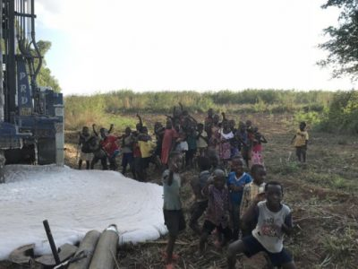 Local children watch new borehole drilling